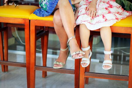 Feet in the summer on colorful red and orange chairs, women's and children's feet, in short and light dresses, Ms., sunny, summer day 新聞圖片