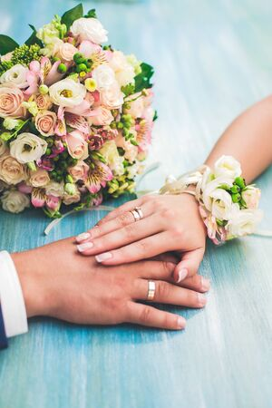 Lovely hands of a loving couple, man and woman, bride and groom, on a light background with a bouquet of beautiful flowers