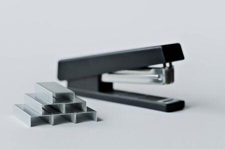 Grapadora negra con clips de papel aislado sobre fondo blanco. Foto de archivo