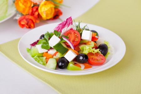heathy diet: Greek salad in the white plate on a green napkin