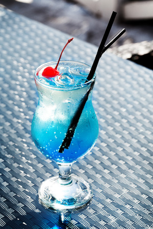 Blue Lagoon cocktail with a cherry in a still life photo