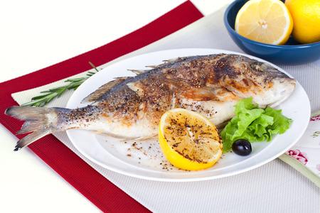 hele vis op een plaat met citroen en olijven in stilleven Stockfoto