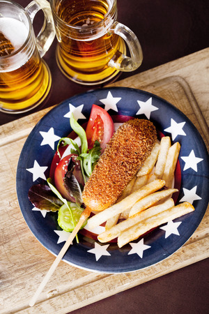 korndog with french fries on a plate in the style of Provence photo