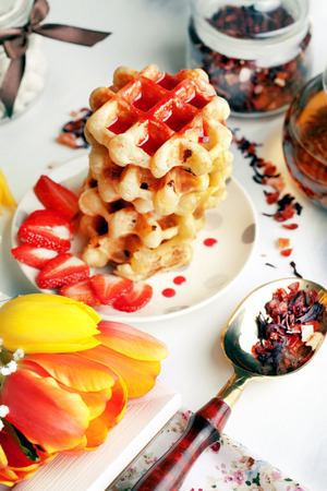 Viennese wafers with strawberry syrup and strawberries with tulips photo