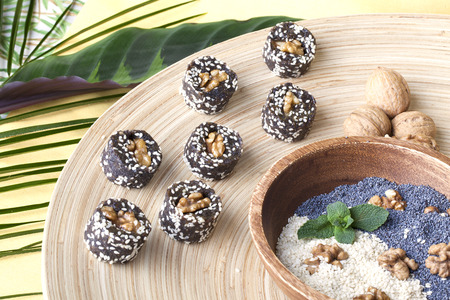 raw food sweets with walnut, poppy seeds, coconut in a still life photo