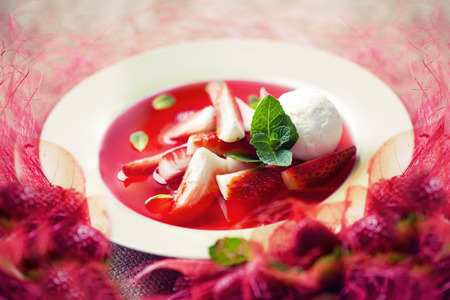 strawberry soup with ice cream and mint on a plate decorated with fresh strawberries photo