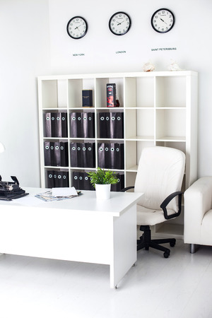 white business office with a desk, a clock and a leather chair photo