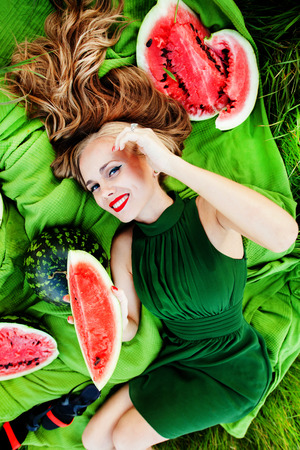 beautiful girl with red lips in the grass with watermelons photo