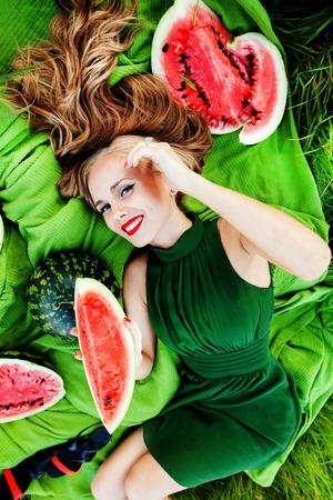 mooi meisje met rode lippen in het gras met watermeloenen