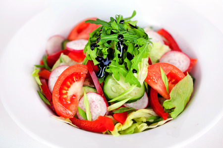 salad with tomato, cucumber, radish, arugula and balsamic sauce closeup photo