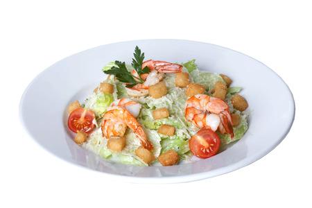 ensalada cesar: Ensalada César con camarones en un plato sobre un fondo blanco