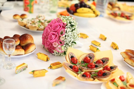 wedding bouquet on a banquet table with sandwiches as ladybirds photo