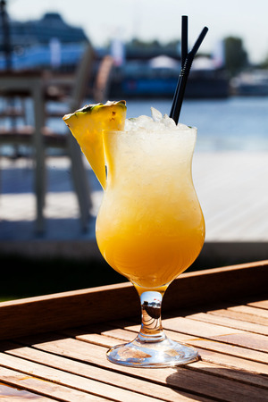 appetizing cocktail with pineapple on a background of water photo