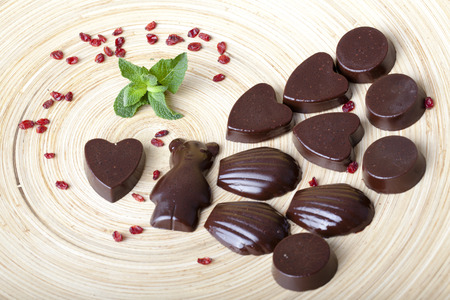 raw chocolates in the shape of bears, hearts, seashells on a wooden plate photo