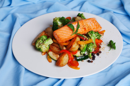 salmon fillet with vegetables and basil on a plate photo