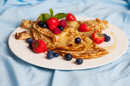 pancakes with mint, strawberries, raspberries, blueberries on a plate photo