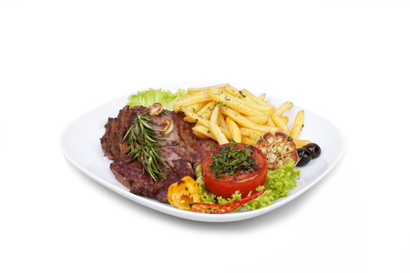 grilled steak with french fries and vegetables on the plate on white background photo