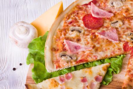 stuk pizza met ham, champignons en kaas op een wit bord