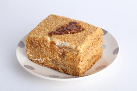 honingkoek met karamel patroon op een plaat op een witte achtergrond Stockfoto