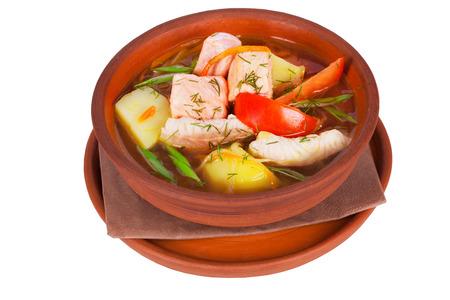 vissoep met rode en witte vis, aardappelen en groenten in een pot op een witte achtergrond voor het menu