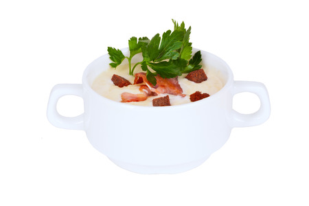 romige soep met croutons en spek peterselie in terrine op een witte achtergrond Stockfoto