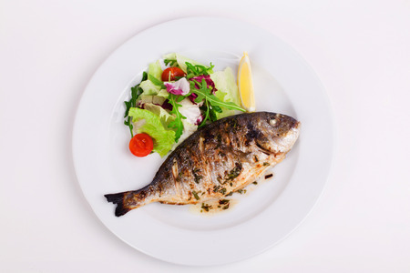 baked whole fish grilled on a plate with vegetables and lemon on top for the menu Foto de archivo