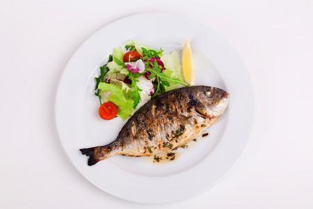 plato de pescado: pescado entero al horno a la parrilla en un plato con verduras y lim�n en la parte superior para el men�
