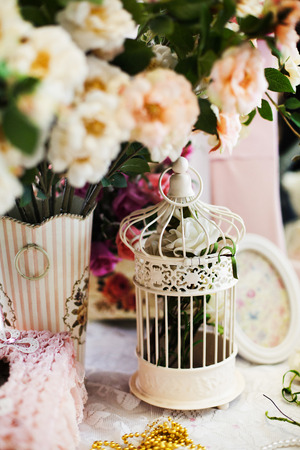 Vintage bird cage in pink romantic still life with flowers photo