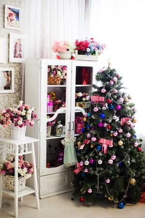 Kerstboom in een oud roze inter met bloemen Stockfoto