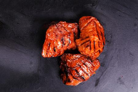 plakjes rundvlees gegrild op een zwarte achtergrond baksel