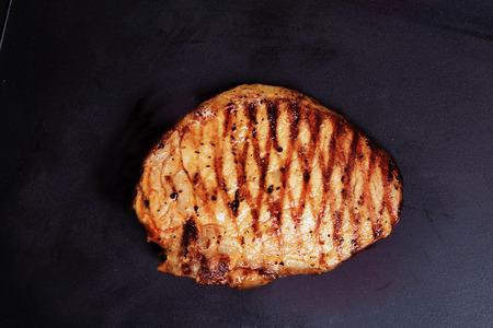 steak van varkensvlees gegrild op een zwarte achtergrond baksel