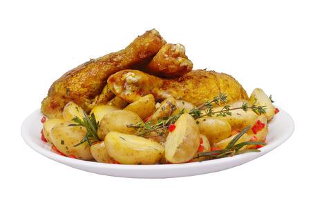 Gebakken kip benen met aardappelen, rozemarijn en tijm met specerijen geïsoleerd op een witte achtergrond voor het menu