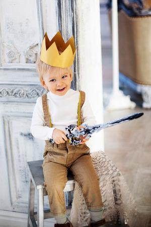 kleine jongen prins met kroon en zwaard in het kasteel gelukkige jeugd