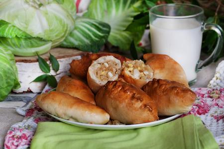 zelfgemaakt gebak met kool in een stilleven, een beker melk, kool, bladeren, greens, berk spil