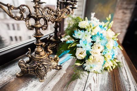 mooie bruiloft boeket met witte en blauwe bloemen op een houten tafel met vintage kandelaars Stockfoto