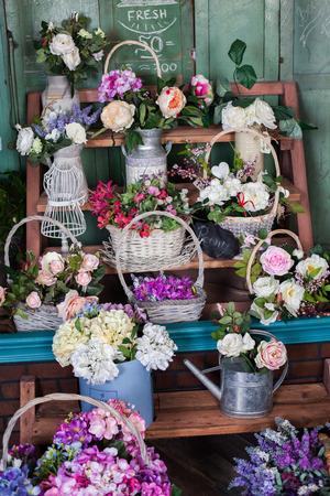 planken met mand van bloemen in een bloemenwinkel, pioenen, rozen, kunstbloemen
