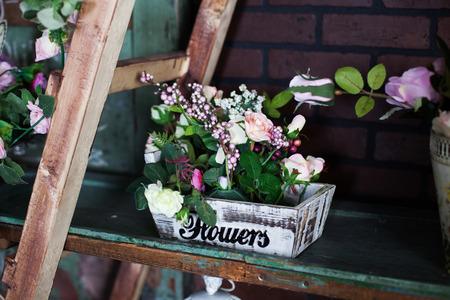 heerlijke mand met Silk bloemen pioenrozen op de plank
