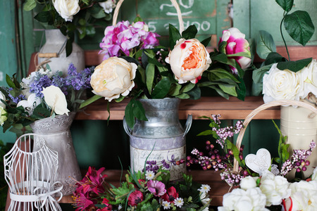 heerlijke ijzeren kruik in de stijl van de Provence met zijden bloemen pioenrozen op de plank Stockfoto