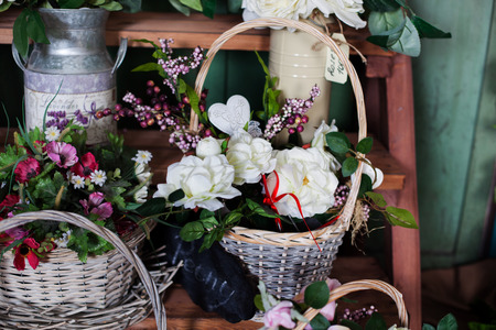 heerlijke mand met bloemen van de zijde pioenen op de plank