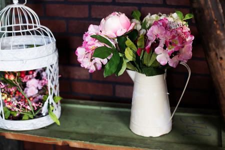 heerlijk ijzer werper in de stijl van de Provence met Silk bloemen pioenen, vogelkooi
