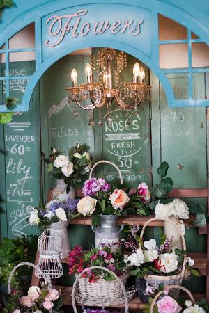planken met mand met bloemen in een bloemenwinkel, pioenrozen, rozen, kunstbloemen Stockfoto