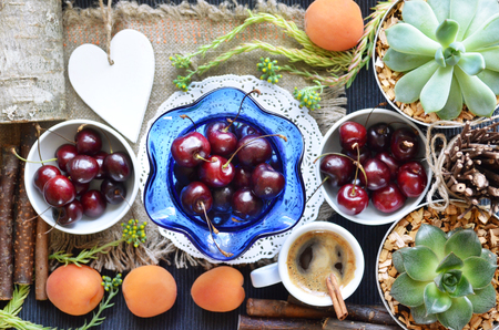Ripe cherries in various dishes and apricots on a dark tablecloth in a rustic setting. Summer berries and fruits. The view from the top.