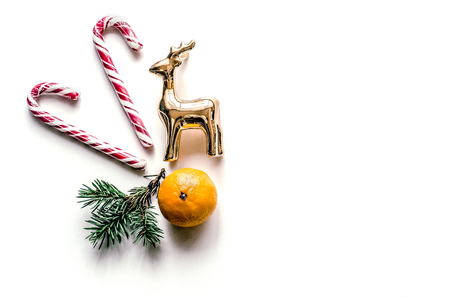New Years unusual composition with spruce branches, sweets, tangerine and deer. Christmas background for presentation of work or text. Beautiful greeting card. View from above. Copy space