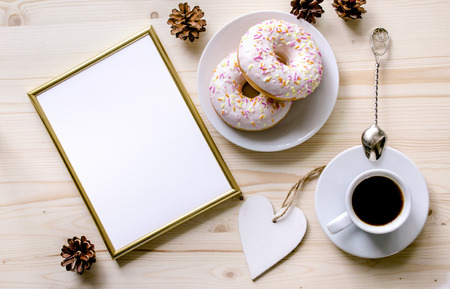 Morning composition with coffee and donuts  on a wooden table. Gold frame for the presentation of works or text. Top view. Copy space. Mock-up 免版税图像