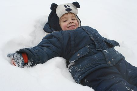 lays: The boy lays on a snow Stock Photo