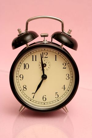 The black alarm clock is on a pink background photo