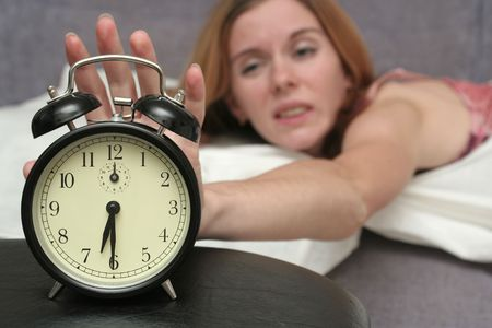 woken: The black alarm clock has woken the girl Stock Photo