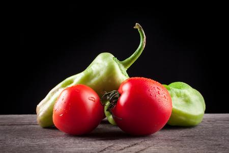 légumes sur un fond noir, les poivrons, les tomates