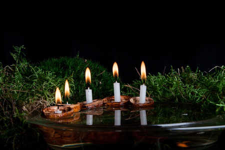 Christmas candles in walnut shell on water surface