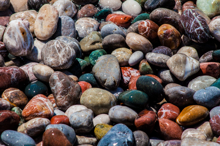 Colored pebbles on the beach and sea wave 免版税图像